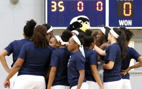 The women's basketball team huddles around Gus before a game last season. They went 13-17.