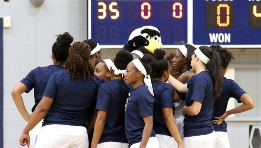The+women%27s+basketball+team+huddles+around+Gus+before+a+game+last+season.+They+went+13-17.