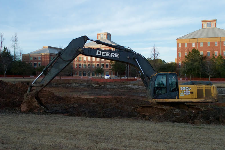 The pond in front of the Nursing and Nursing/ Chemistry and College of Education building remains under construction. Piles of sediment is scooped from the bottom of the ponds to increase its depth. Photo by Matthew Enfinger