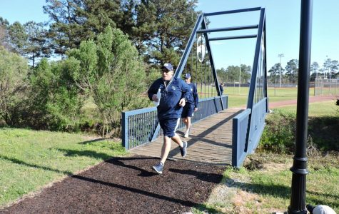 Head Coach Chad Lunsford runs across the bridge at Eagle Creek for the first practice of spring.
