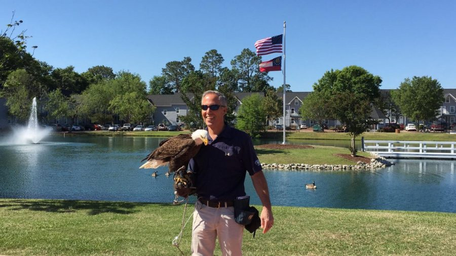 Wildlife Center Director Steve Hein holds Freedom the Eagle in front of the U.S. flag at the Flag Ceremony. The ceremony was held at University Villas, one of eight Georgia Southern University housing complexes.