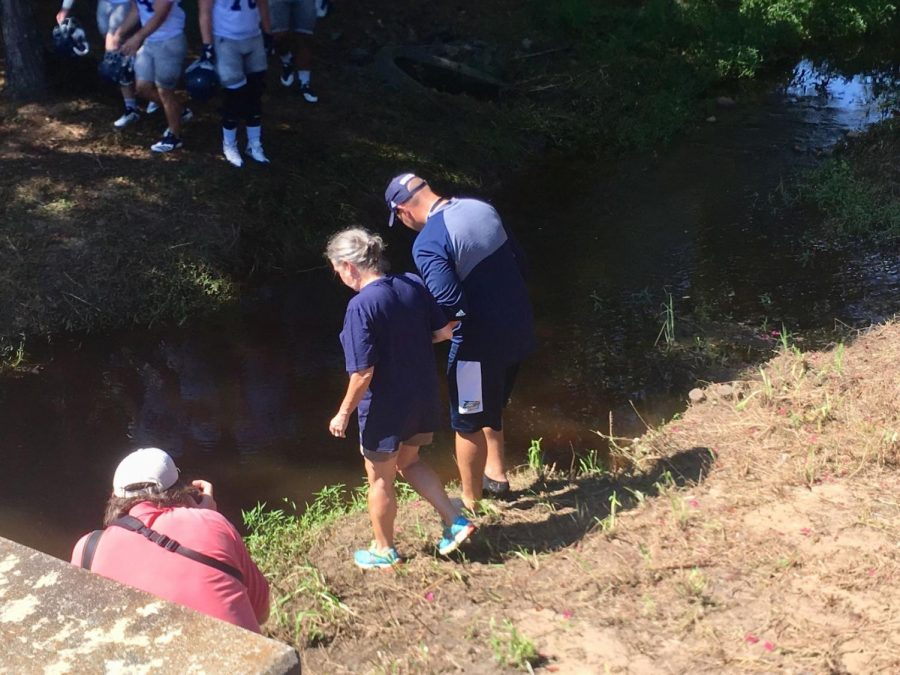 Head+football+coach+Chad+Lunsford+and+Interim+President+Shelly+Nickel+stood+on+the+banks+of+the+creek+before+stepping+in