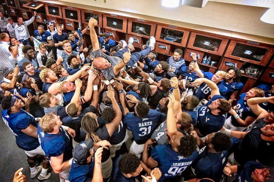 This picture of Lunsford crowd surfing with his team after the 52-0 victory over South Alabama is on Lunsford's wall in his office.