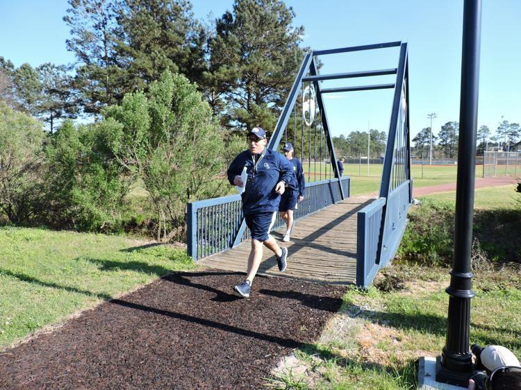 Lunsford led the team across the bridge at Beautiful Eagle Creek to mark the start of spring football practice.