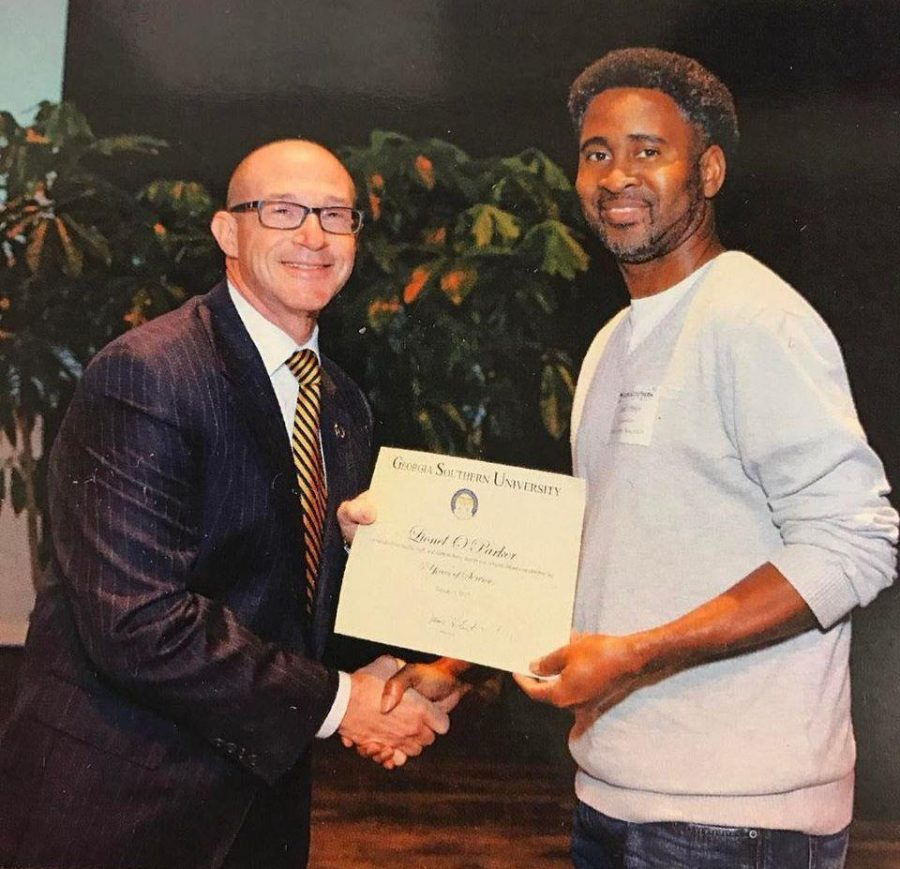 Lionel Parker (right) receives a service award from former GS President Jaimie Hebert (left). Parker received the award for ten years of service at GS.