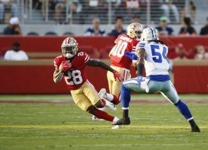 San Francisco 49ers' Jerick McKinnon (28) runs away from Dallas Cowboys' Jaylon Smith (54) in the first quarter of their preseason NFL game at Levi's Stadium in Santa Clara, Calif., on Thursday, Aug. 9, 2018.