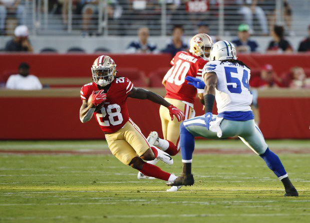 San Francisco 49ers' Jerick McKinnon (28) runs away from Dallas Cowboys' Jaylon Smith (54) in the first quarter of their preseason NFL game at Levi's Stadium in Santa Clara, Calif., on Thursday, Aug. 9, 2018.