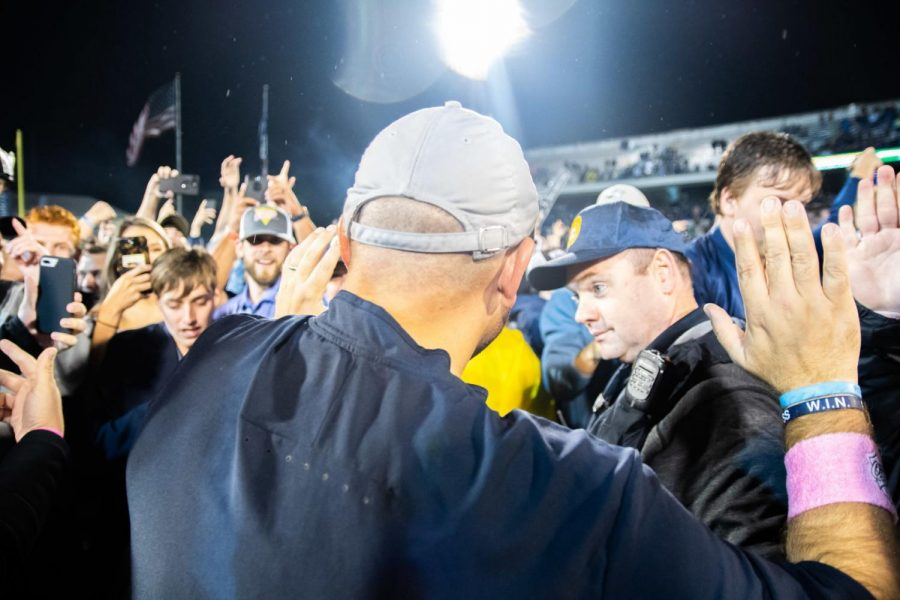 Head+Coach+Chad+Lunsford+celebrates+the+win+over+Appalachian+State+with+the+students+who+had+stormed+the+field.
