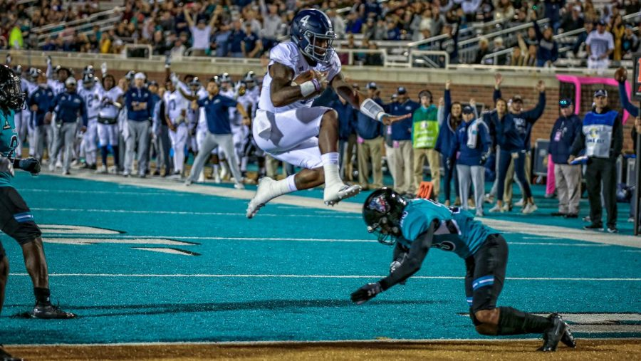 Redshirt-sophomore quarterback Shai Werts hurdles a Coastal Carolina defender in the 41-17 against the Chanticleers.