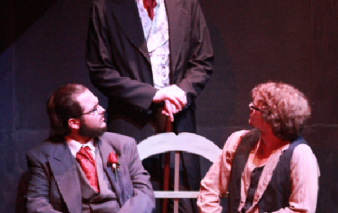 "Berlioz played by Jacob Whitfield (seated left), Woland played by Andrew Shepherd (middle) and Ivan played by Nicholas Parrish (right) discuss their beliefs on Jesus Christ in a scene from ""The Master and Margarita."""