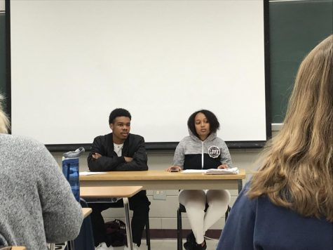 Two students sit at the front of the classroom, acting as mediators.