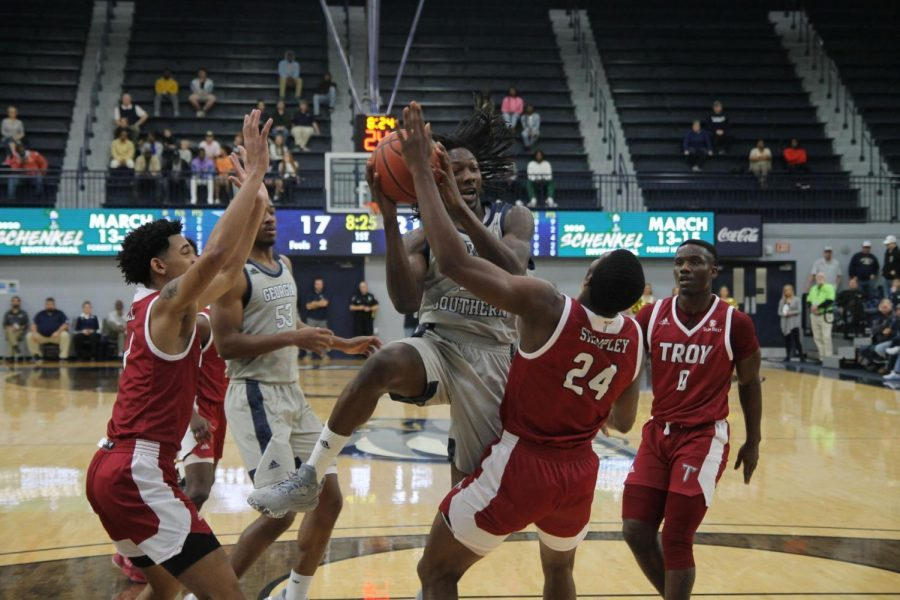 Quan Jackson pulls up for two against a Troy defender during Thursday's game. Both basketball teams suffered losses over the weekend, but the Georgia Southern track & field team had strong perfomances on the road.