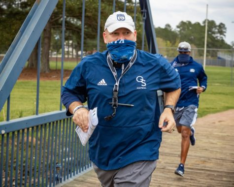 Chad Lunsford runs with his team over the Beautiful Eagle Creek bridge to get to the practice field on March 24. Eagle Creek is said to have magical properties by legend coach Erk Russel, and the drainage ditch named Beautiful Eagle Creek has since become an important part of game day traditions.