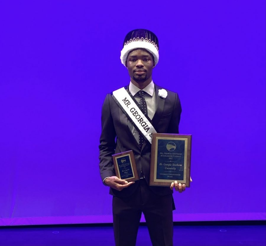 Shahad Smith stands with his awards after being crowned 2021